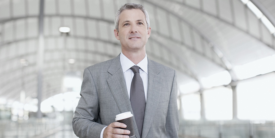 businessman walking holding coffee