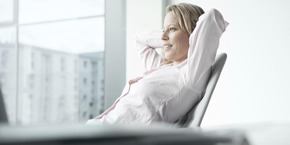 businesswoman relaxing behind desk